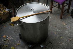 Large aluminium pot with the gas cylinder in the camp kitchen. Preparing traiditional food in metal cauldron. Big wooden spoon on top of pot.