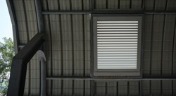 Large aluminum lattice vents in the rectangular frame at the eaves.