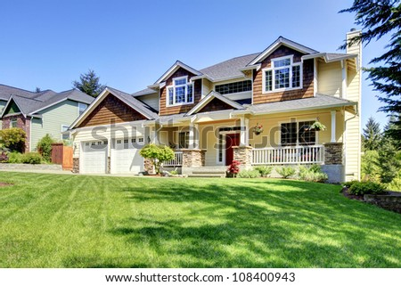 Large American beautiful house with red door and two white garage doors.