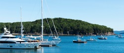 Large and small boats docked and moored on a Sunday morning in late July in the waters of Bar Harbor Maine.