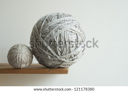large and small size balls of wool on desk
