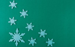 Large and small white snowflakes on a greenish background. Greenish background with white snowflakes