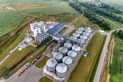 Large animal feed factory. Grain warehouse, granary. Large steel towers for storing crops. Aerial view, cloudy day.