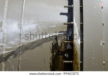 large aqueduct water pipe leaking from a bolted joint - stock photo