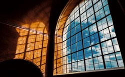 Large arched window has blue sky on background and beautiful shadows from sunlight on the yellow wall. Indoor interior in castle. Beautiful abstract picture. Postcard concept.