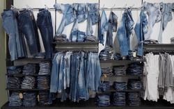 Large assortment of jeans denim trousers and shirts hanging or arranged on the shelf of a clothing store