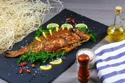 Large baked carp with herbs, lemon and spices. top view, place for text.