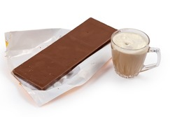 Large bar of the milk chocolate lies on an opened partly crumpled paper wrapper and coffee drink in glass cup on a white background