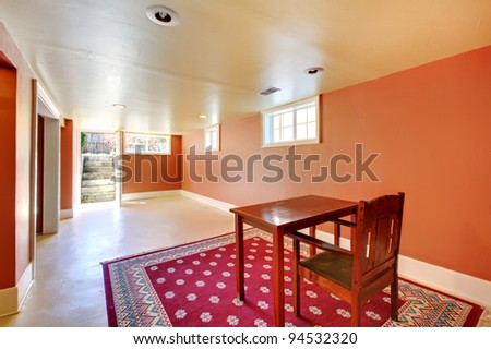 Large basement room with desk and red rug. - stock photo