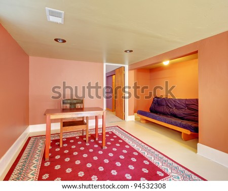 large basement room with red rug and orange walls stock photo 94532308