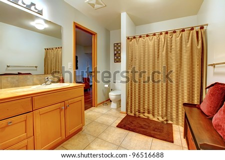 Large bathroom interior with bench with red pillows and shower curtain. Wood cabinet with one sink.