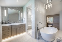 large bathroom with white fixtures tiles oval bathtub and glass walls