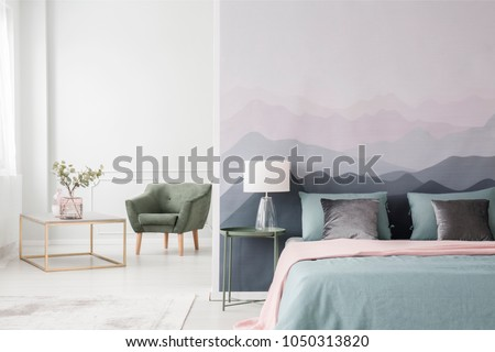 Large bed with blue sheets and a pink blanket by a landscape wallpaper in a cozy, modern bedroom interior #1050313820
