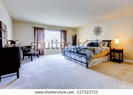 Large bedroom interior with beige carpet and black bed. - stock photo