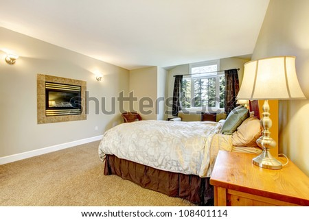Large bedroom with fireplace and nightstand with lamp and brown carpet. - stock photo