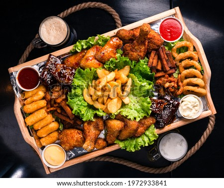 Large beer plate, large set of beer snacks. assorted snacks deep-fried beer. Food for a holiday for a large company. hot meat snacks for beer served on wooden dish board top view, flat lay