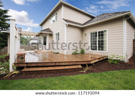 Large beige house with porch from the backyard with grass and mulch.