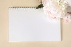 Large beige-pink peony flower and spring-loaded notebook on light paper background Image for design of greeting cards on theme of wedding, Mother's Day, birthday and other greetings. Copy space