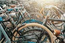 Large bicycle parking in Amsterdam, many bikes in sunlight, toned
