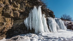 Large bizarre icicles hang from the slope of the granite rock. Cracks in the stones. Snow on the ground. Clear blue sky. Siberia