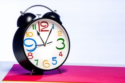 large black alarm clock with large numbers of many colors and different sizes, with background, red and white, horizontal format