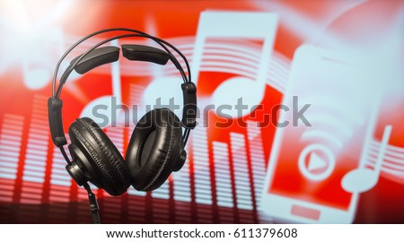 Large black headphones in front of a modern blurred background with notes, equalizer and a smartphone icon. An abstract online music streaming and listening concept with free copy space for text.  Stock photo ©