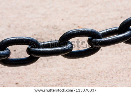 Large black metal chain with a stone color background - stock photo