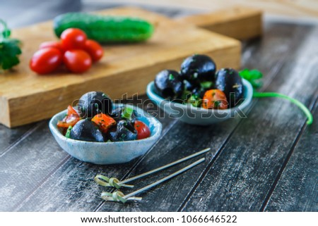 Large black olives, cherry and parsley under marinade in a ceramic bowl side view horizontal #1066646522