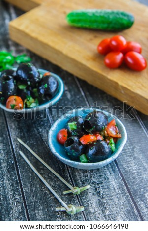 Large black olives, cherry and parsley under marinade in a ceramic bowl vertical #1066646498