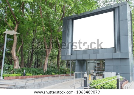 Large blank outdoor TV screen, LED panel, advertising lightbox at the park beside some trees and bushes  for mock ups.
