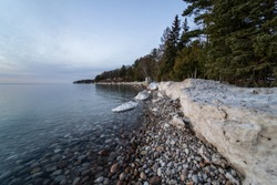 Large blocks of ice across the shoreline during beautiful sunset. Canadian winter.