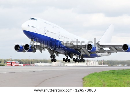 Large blue and white passenger airplane takes off at airport.
