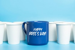 Large blue cup surrounded by white paper cups on a blue background. Concept boss, unique, friendly team, fimenism. Copy space. Added text Happy Boss's Day