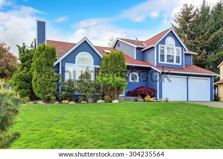 Large blue house with white trim, and well kept lawn, along with two garage spaces.