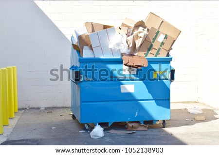Large blue Recycle dumpster full of recyclable materials