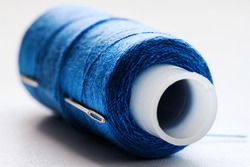Large bobbin with dark blue sewing thread lying on white table for handicraft work. Concept tailor equipment and accessory.