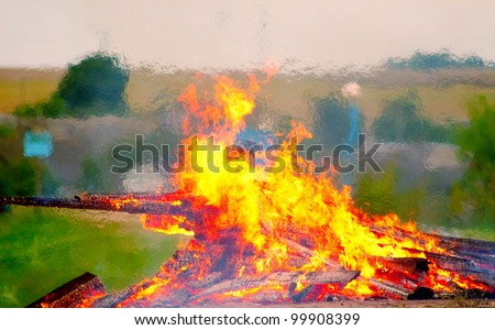 Large bonfire burning with large logs on the background of the beach