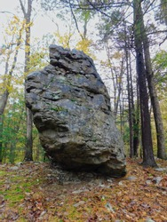 Large boulder balanced on end within a woodland setting.  Image taken at Trough Creek State Park in Pennsylvania in the autumn.