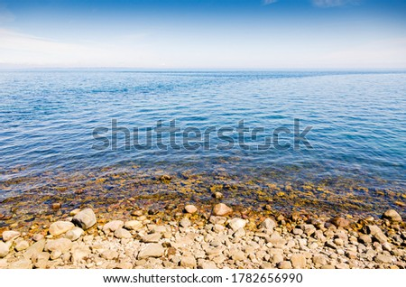 Large boulder rocks on the beach in the blue ocean on the coast of Denmark. Stockfoto ©