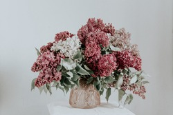 large bouquet of lilac in a pink glass vase on a light background. the concept of welcoming spring. lilac flower bouquet.