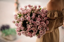 large bouquet of small pastel purple roses in hands of woman in a beige dress.