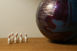 Large bowling ball against miniature pins