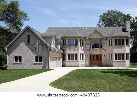 Large brick home in suburbs with three car garage