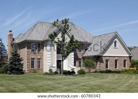 Large brick home with cedar shake roof