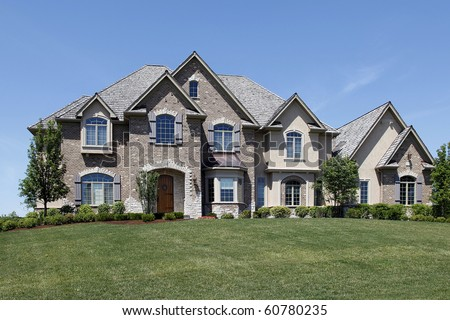 Large brick home with stone entry and wooden door