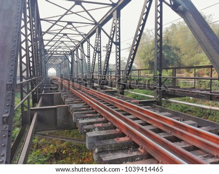 Large bridges are made of strong steel with rust on the surface and structure. Used for trains and vehicles, travel between the outback, freight, fuel and woodland. #1039414465