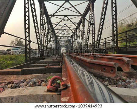 Large bridges are made of strong steel with rust on the surface and structure. Used for trains and vehicles, travel between the outback, freight, fuel and woodland. #1039414993