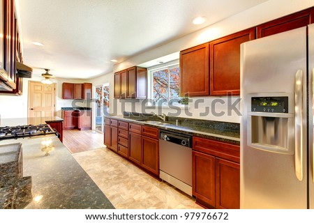 Large bright kitchen with dark cherry cabinets and stainless steal appliances.