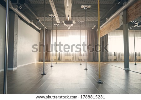 Large bright room with vertical poles for dancing, big mirrors and window with curtains Сток-фото ©