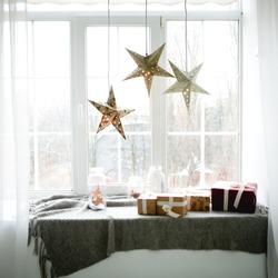 Large bright window. On the window-sill is a gray knitted plaid with gifts and sparkles with herlands. Paper Christmas stars are suspended on the background of the window.